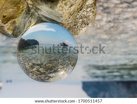 Crystal ball in the man's hand. Original upside down view and rounded perspective of the sky, sea and boat.Original and engaging picture.