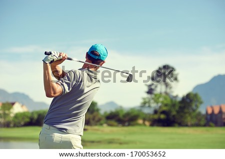 Golfer hitting golf shot with club on course while on summer vacation
