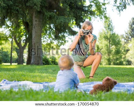 Mid adult mother photographing baby boy during picnic at park #170054870