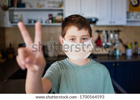 Victory sign shown by boy wearing surgical mask #1700564593