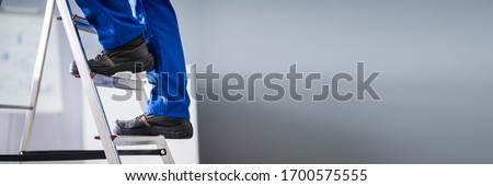 Step Ladder Safety. Worker Man In Shoes #1700575555