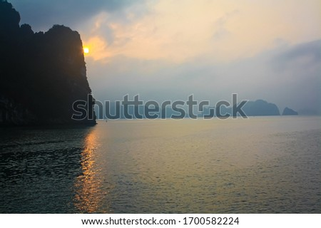 Pictured here is the sun setting over Ha Long Bay, Vietnam during a river cruise. The sun reflects in the water and peeks out from behind the infamous geographical rock formations.