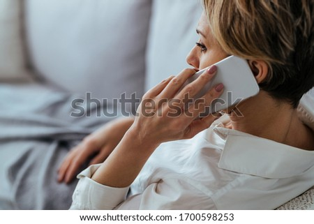 Distraught woman resting on the sofa and communicating over mobile phone/  #1700598253