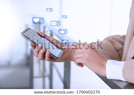 Young woman using modern smartphone indoors, closeup #1700602270
