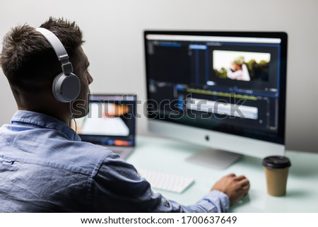 Young man video editor with works with footage on his personal computer with big display in office
