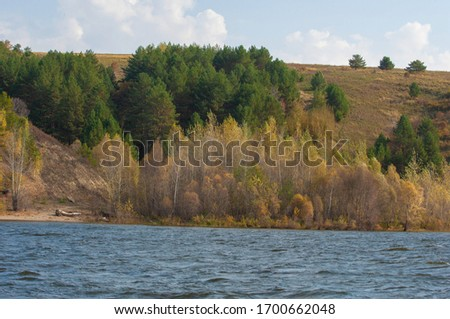 Autumn landscape, dark blue water, last warm days, river, trees, windy weather, yellow-red autumn leaves #1700662048