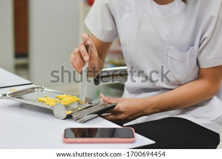 Pharmacist is counting pills on counting drugstore,Pills in pill counting tray,Orange tablets medicine on the drug count tray,Tablets medicine on the drug count tray, #1700694454