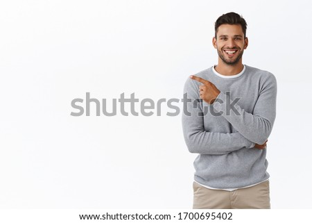 Man praising great concept, pointing left at your project as discuss corporate staff coworker. Attractive pleased businessman in grey casual sweater having chat and recommend check-out product #1700695402