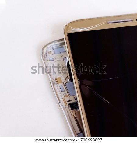 damaged smart phone with cracked display, white background