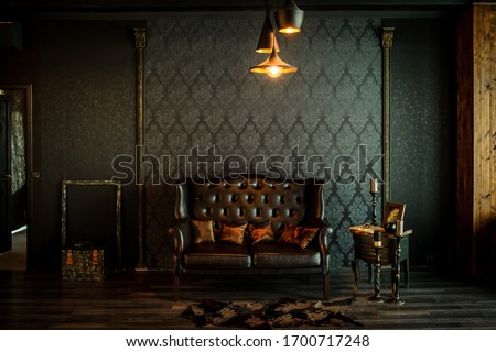 Old vintage interior with leather sofa, wood table and ceiling light. Royalty-Free Stock Photo #1700717248