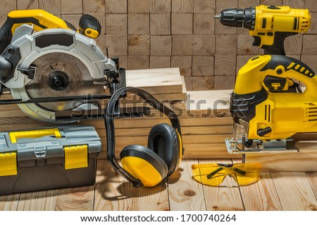 construction carpentry electric hand tools on wooden background Royalty-Free Stock Photo #1700740264