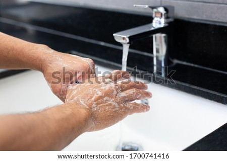 Man is washing his hands in a sink sanitizing the colona virus for sanitation and reducing the spread of COVID-19 spreading throughout the world, Hygiene ,Sanitation concept. #1700741416