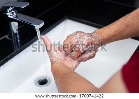 Man is washing his hands in a sink sanitizing the colona virus for sanitation and reducing the spread of COVID-19 spreading throughout the world, Hygiene ,Sanitation concept. #1700741422