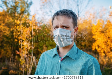 A man in a medical mask on the background of trees #1700756515
