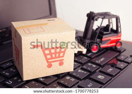 Forklift lift parcel carton box with shopping trolley cart printing on laptop computer with white wall background. E-commerce, online shopping, logistic inventory control, cash on delivery (COD), b2c. #1700778253