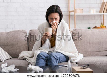 Contagious disease outbreak. Sick girl with hot drink suffering from virus at home Royalty-Free Stock Photo #1700809078