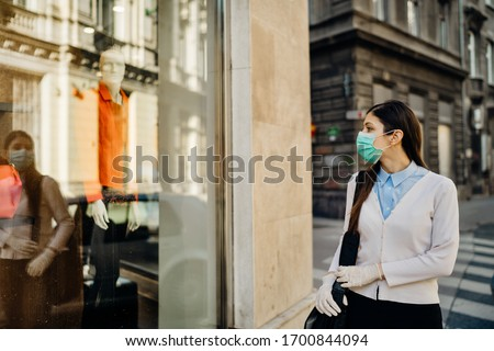 Woman with mask looking at a closed fashion clothes storefront.Clothing shopping during coronavirus outbreak shutdown.COVID-19 quarantine apparel retail store closures.Small business loss concept. #1700844094