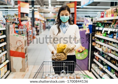 Woman with mask safely shopping for groceries amid the coronavirus pandemic in a stocked grocery store.COVID-19 food buying in supermarket.Panic buying,stockpiling.Food shortage.Lockdown preparation.