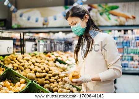 Woman with mask safely shopping for groceries amid the coronavirus pandemic in a stocked grocery store.COVID-19 food buying in supermarket.Panic buying,stockpiling.Shortage of fresh produce,vegetables #1700844145