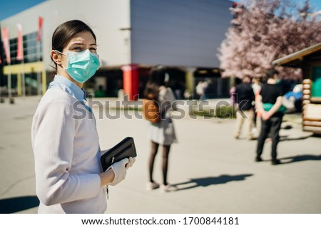 Shopper with mask standing in line  to buy groceries due to coronavirus pandemic in grocery store.COVID-19 shopping safety measures,social distancing.Quarantine preparation.Panic buying.Long queue #1700844181