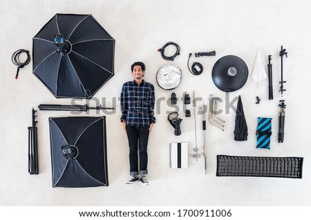 Aerial top view or flat lay Asian photographer with many photography equipment and professional studio photo shooting tool lying on white floor background use for header or banner of camera concept.