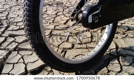 The front wheel of a school bike against a background of dried up cracked clay soil. Racing in the desert. Close-up bicycle rubber tire and metal aluminum knitting needles. Wheel mount. Bolt and nut #1700950678