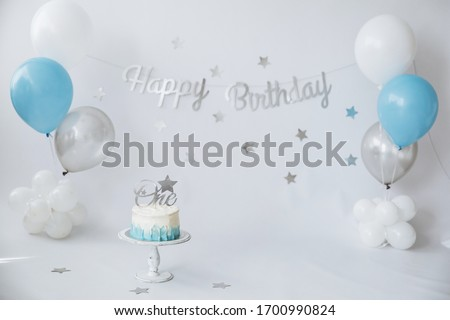 Festive background decoration for birthday celebration with gourmet cake and blue balloons in studio, cake smash first year concept Royalty-Free Stock Photo #1700990824