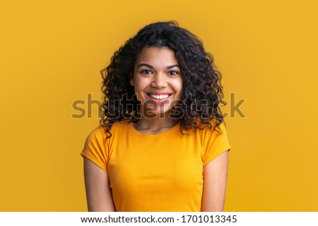 Portrait of young attractive african american woman on bright background. Cute girl with voluminous curly hair looking happy with wide perfect smile on her face.
