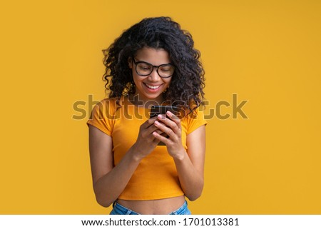 Half-length studio portrait of beautiful casually dressed dark skinned girl with perfect charming smile texting message via her mobile phone isolated on bright colored yellow background.