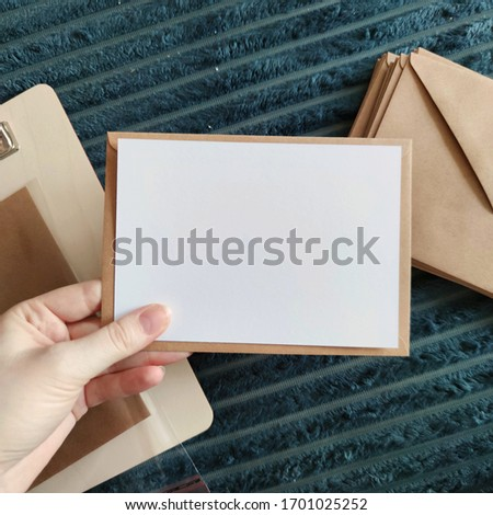 a6 Postcard mockup, woman's hand holding a blank card mid-air with a triangle closing brown Kraft paper envelope on grey blanket background with wooden clipboard and shipping supplies, packaging #1701025252