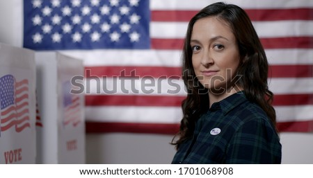 """MCU profile Caucasian American woman in plaid shirt wearing """"I Voted"""" sticker while standing proud in front of US flag next to polling booths #1701068908"""