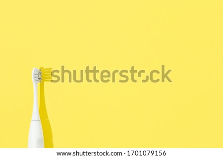 Sonic toothbrush or electronic toothbrush on yellow pastel background.