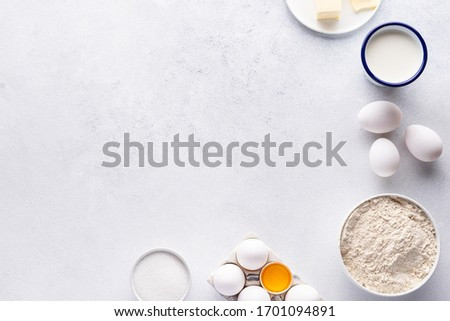 Ingredients for baking and Breakfast (eggs, flour, sugar, milk and butter) on a gray background. Concept: delicious and healthy food. #1701094891