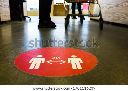 Red round sign printed on ground at supermarket cash desk register informing people to keep 2 meter 6 feet distance from each other,prevent spreading Coronavirus COVID-19 virus disease infection,UK&US