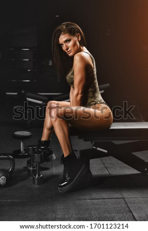 Side view of a girl in sportswear doing exercise with a dumbbell on biceps leaning on a sports bench. Woman doing leisure exercise between exercises in the upper body gym on the background of the gym #1701123214