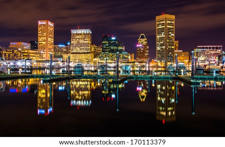 The skyline and docks reflecting in the water at night, in the Inner Harbor of Baltimore, Maryland.