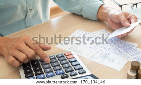 The butler is pressing the calculator calculate the various costs that must be paid by the bill. Many invoices held and placed on the table Royalty-Free Stock Photo #1701134146