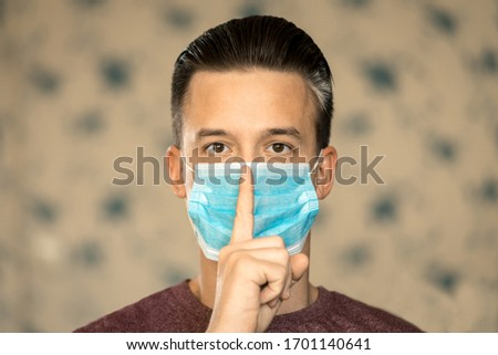 Theme of coronavirus and safety. A young man in a blue virus mask shows his finger a sign of silence. #1701140641