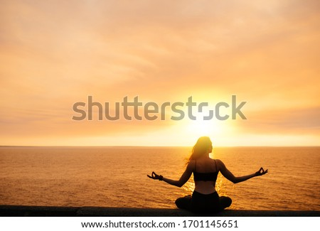 A girl practices yoga by the sea during a beautiful sunset. She is  sitting in lotus position and meditating #1701145651