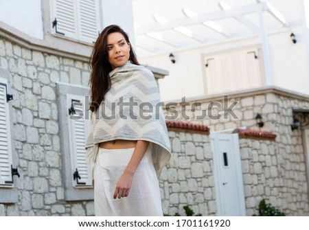 beautiful brunette woman in chic white loose pants and covered herself with a shawl, posing in front of a house. #1701161920