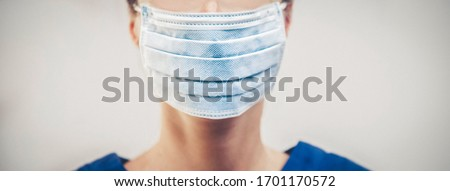 Doctor wearing protection face mask against coronavirus. Banner panorama medical staff preventive gear. Royalty-Free Stock Photo #1701170572
