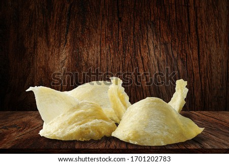 The nest of Edible-Nest Swiftlet, raw edible bird's nest materials tradition chinese medicine. Edible nest soup is popular at Hong Kong, Taiwan, China and Southeast Asia. Edible bird's nest on wood BG #1701202783