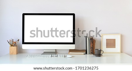 Computer monitor with white blank screen putting on white working desk surrounded by pencil holder, mouse, keyboard, books, coffee cup and picture frame over white wall as background.
