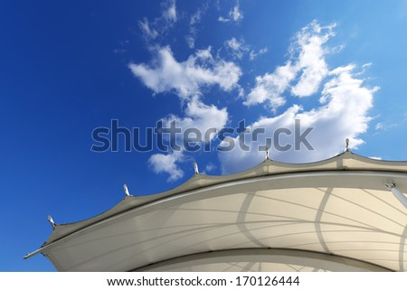 Tensile Structure / Tensile membrane fabric roof with blue sky and clouds in the background. #170126444