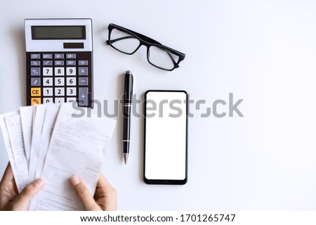 Young woman holding bills and calculating expenses at home, Top view Royalty-Free Stock Photo #1701265747