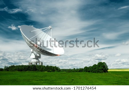 White Radio Telescope, a large satellite dish on a background of blue sky, radar. Technology concept, search for extraterrestrial life, wiretap of space. Mixed medium, copy space Royalty-Free Stock Photo #1701276454