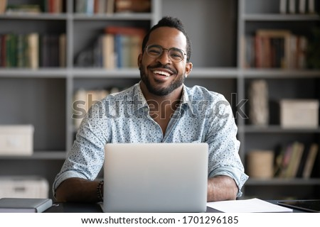 Portrait of smiling African American man in glasses sit at desk in office working on laptop, happy biracial male worker look at camera posing, busy using modern computer gadget at workplace #1701296185