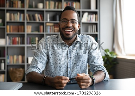 Headshot portrait of happy african American man in glasses sit at desk have video call on gadget, smiling biracial young male in spectacles talk speak on web, using online dating service application #1701296326