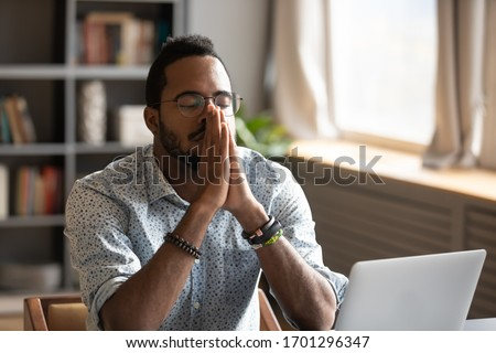 Hopeful African American male believer sit at desk pray to God ask beg for good luck, thoughtful biracial superstitious man hold hands in prayer feel grateful thankful, faith, religion concept #1701296347