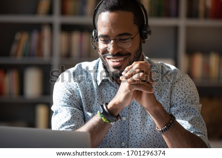 Smiling African American man in headset watch webinar or training on modern computer, happy biracial male call center agent or telemarketer work consult client online, good customer service concept #1701296374